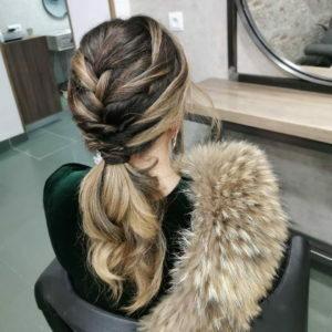 Peinado de fiesta con coleta trenzada en cabello largo rubio que hace destacar el color aplicado en Lucia Estilismo